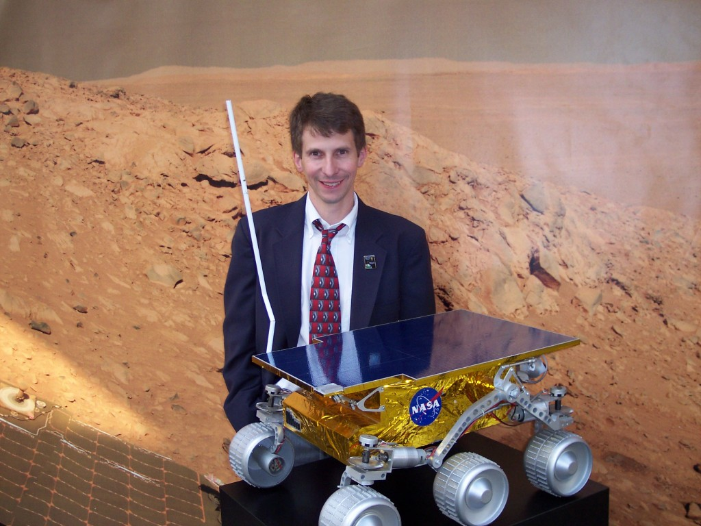 Tom Hill standing behind a model of the Pathfinder Mars Rover