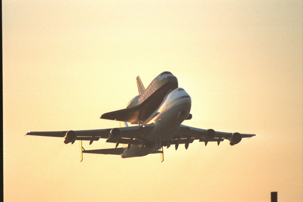 Space Shuttle Endeavour on the back of a 747 takes off in front of a golden sunrise
